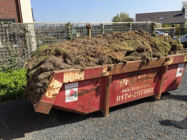 Verwijderde graszoden in de afvalcontainer